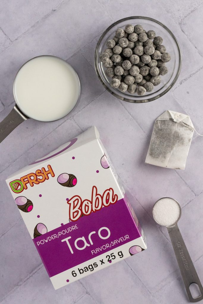 Overhead view of the ingredients needed for bubble tea: boba, milk, a tea bag, sugar and pack of taro powder