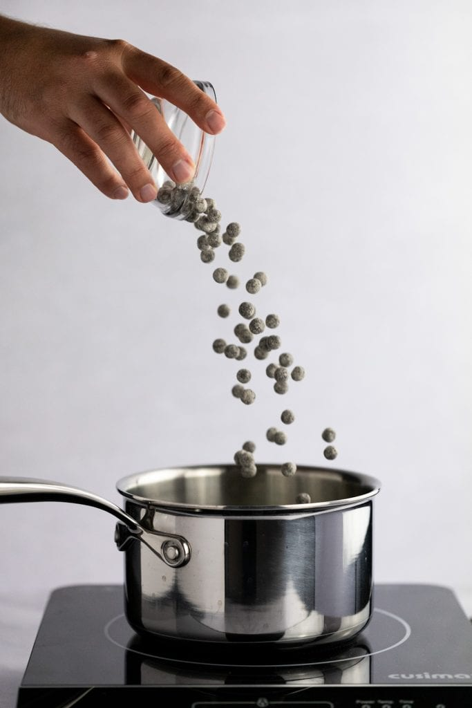 Action shot of a hand pouring a small bowl of uncooked boba into a pot of water on the stove.