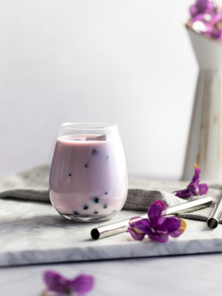 Taro bubble tea on a white marble board with metal bubble tea straws and a vase of purple flowers in the background.
