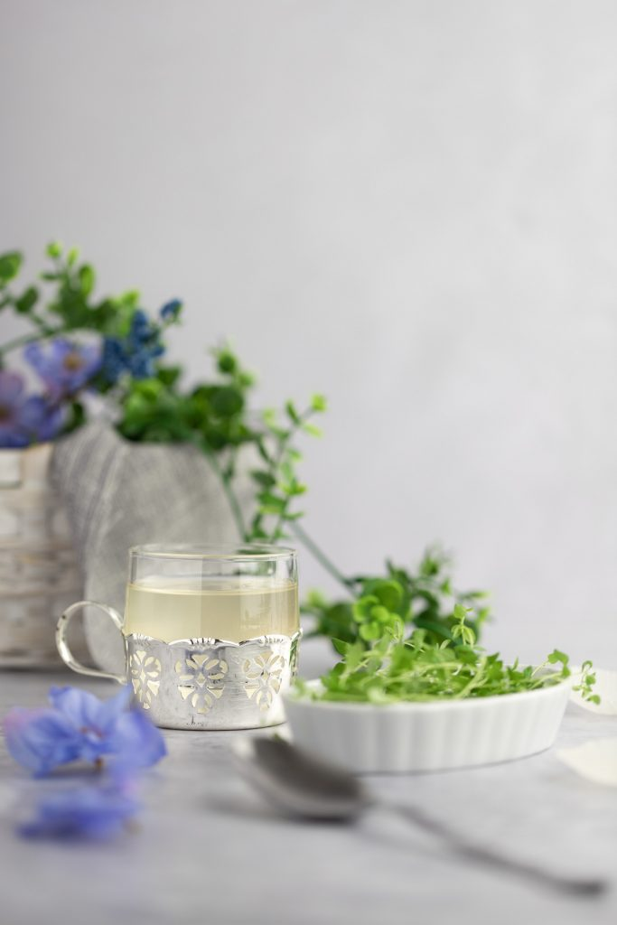 Thyme simple syrup in a small container sitting in a metal carved cupholder, next to a white dish with fresh thyme, and blue flowers in the background.