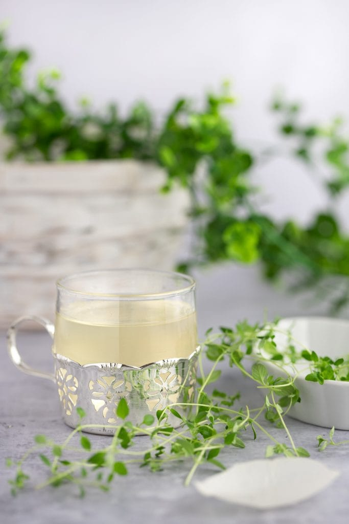 A small container of thyme syrup next to fresh thyme, with green herbs and a white basket in the background.