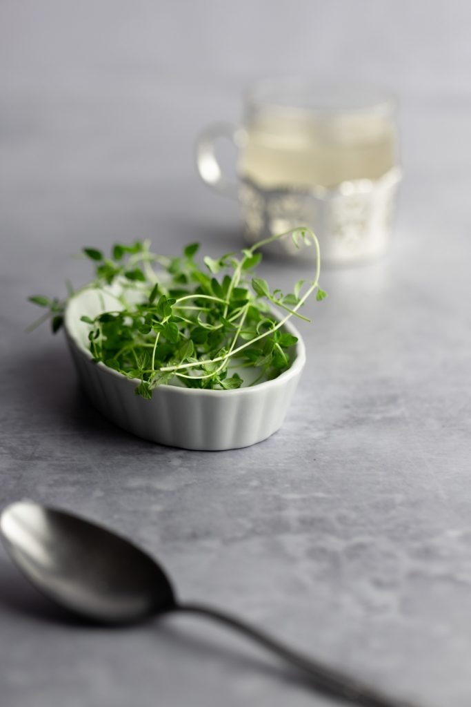 White dish holding fresh thyme sprigs, a metal spoon in the foreground and a small jar of thyme simple syrup in the background.