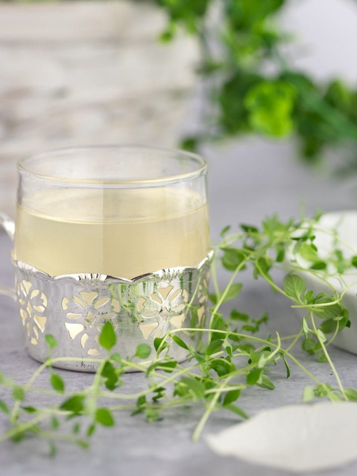 A small glass of thyme simple syrup in a lace metal holder, next to fresh thyme.