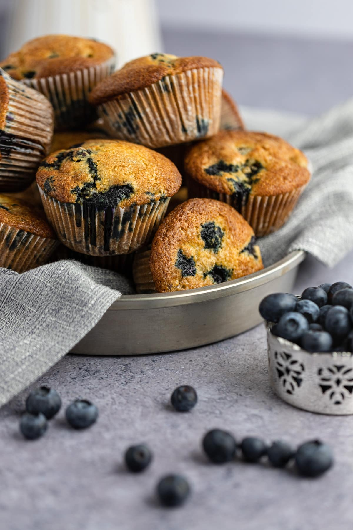 A pile of to die for blueberry muffins on a grey napkin in a round metal tin, with a silver pot of blueberries beside it and some blueberries scattered on the table.