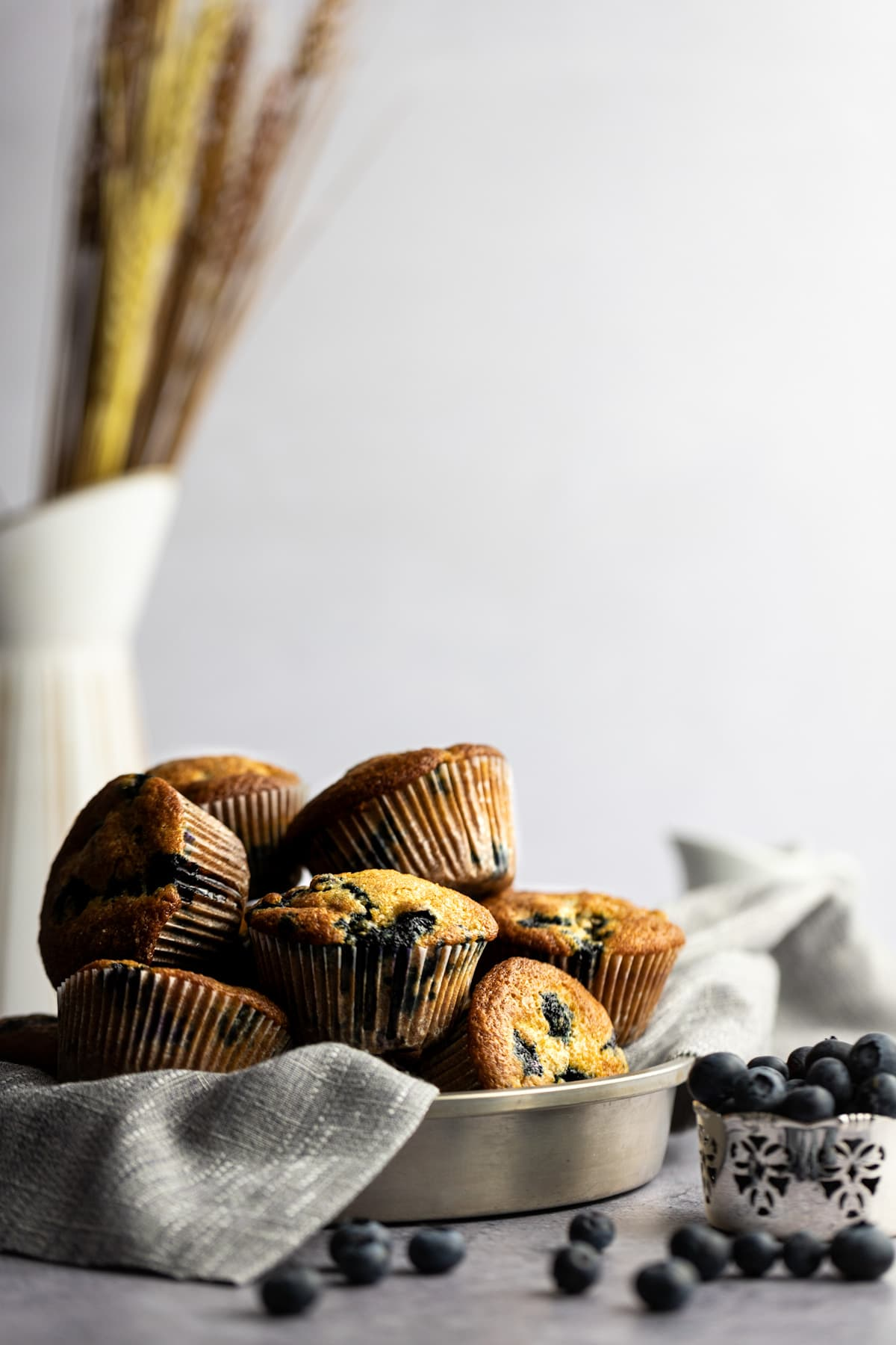 A round metal tin full of a stack of freshly baked golden muffins, next to scattered blueberries, with a white vase holding wheat in the background.