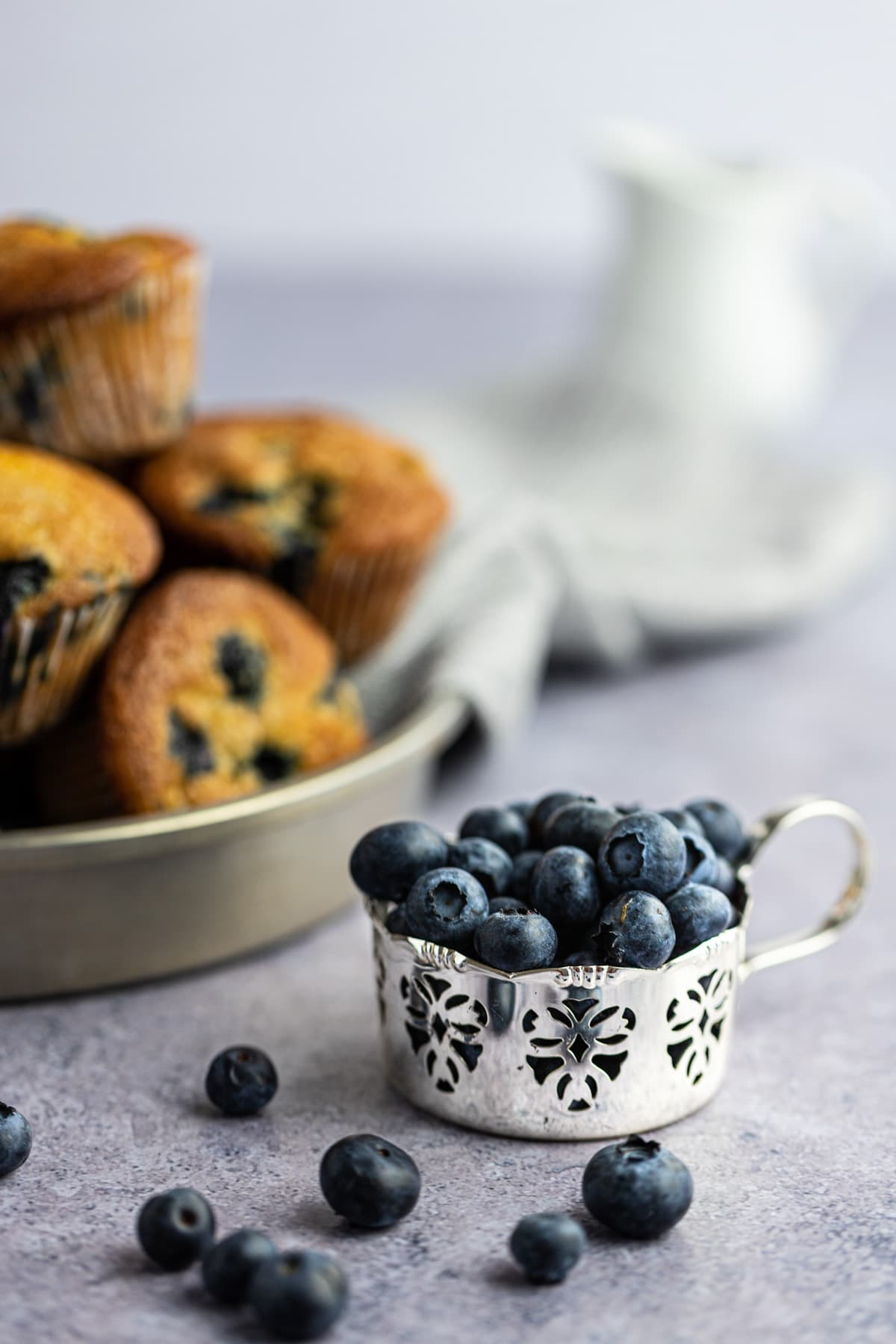 Close up photo of a silver laced cup filled with fresh blueberries, a tin of muffins out of focus in the background.