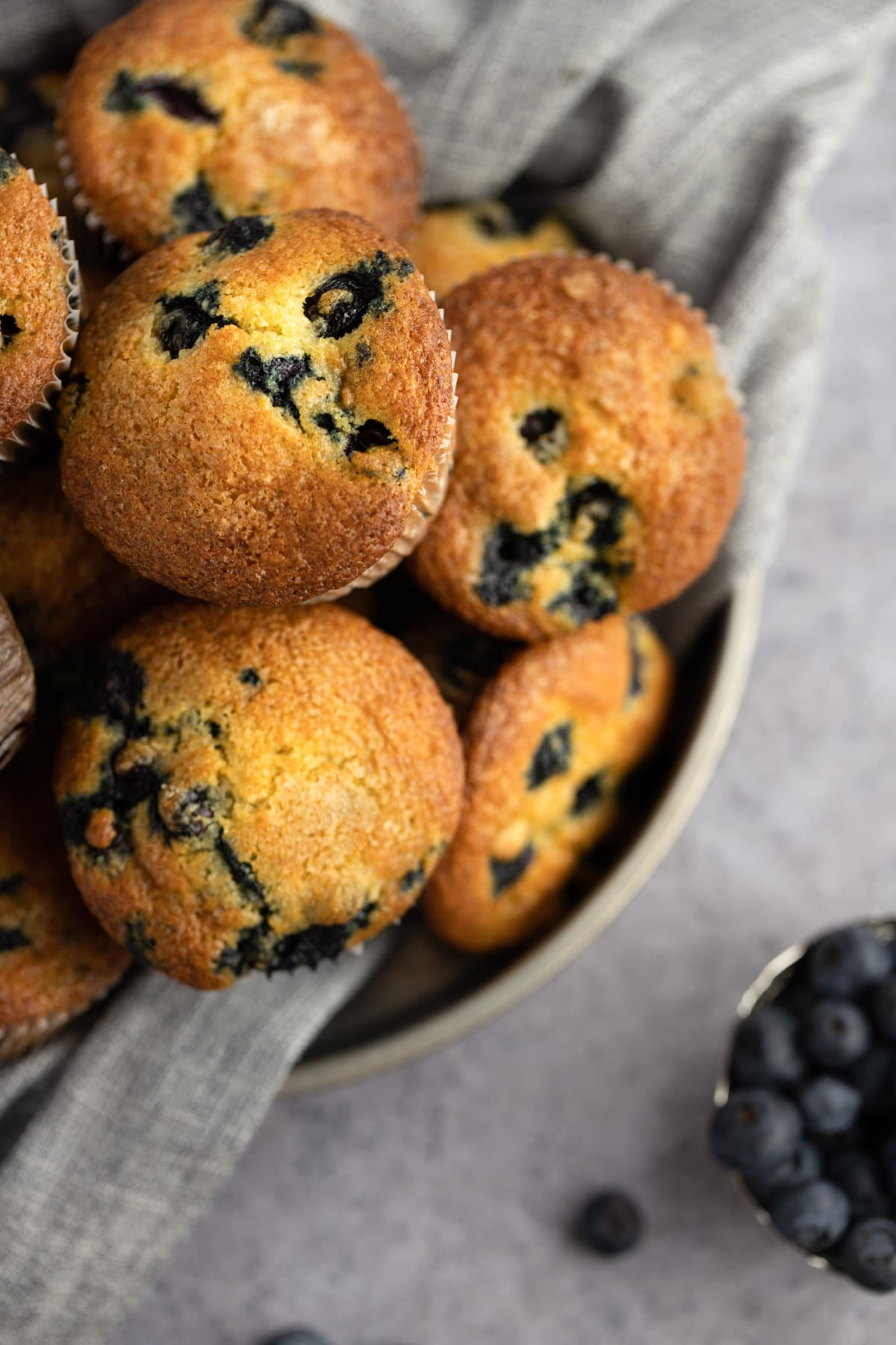 Overhead photo of crispy blueberry muffins on a grey background, with blueberries scattered around it.