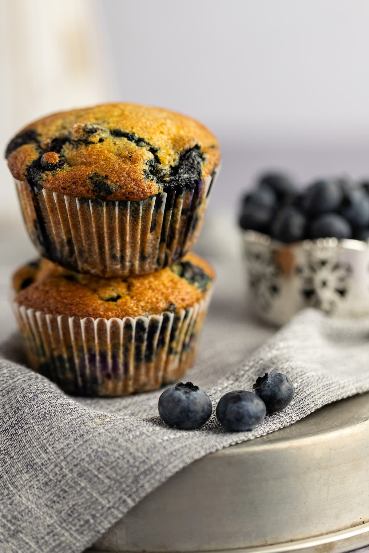 Two muffins stacked on top of each other on a grey napkin on a metal tin, with three fresh blueberries beside them.
