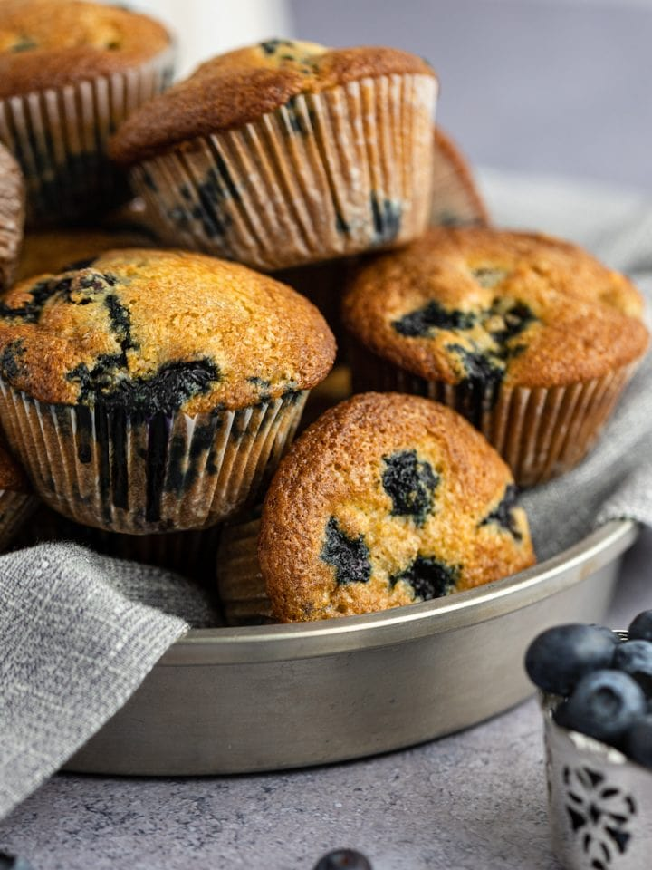 A stack of to die for blueberry muffins on a grey napkin in a round metal tin, next to a silver cup holding a bunch of fresh blueberries.