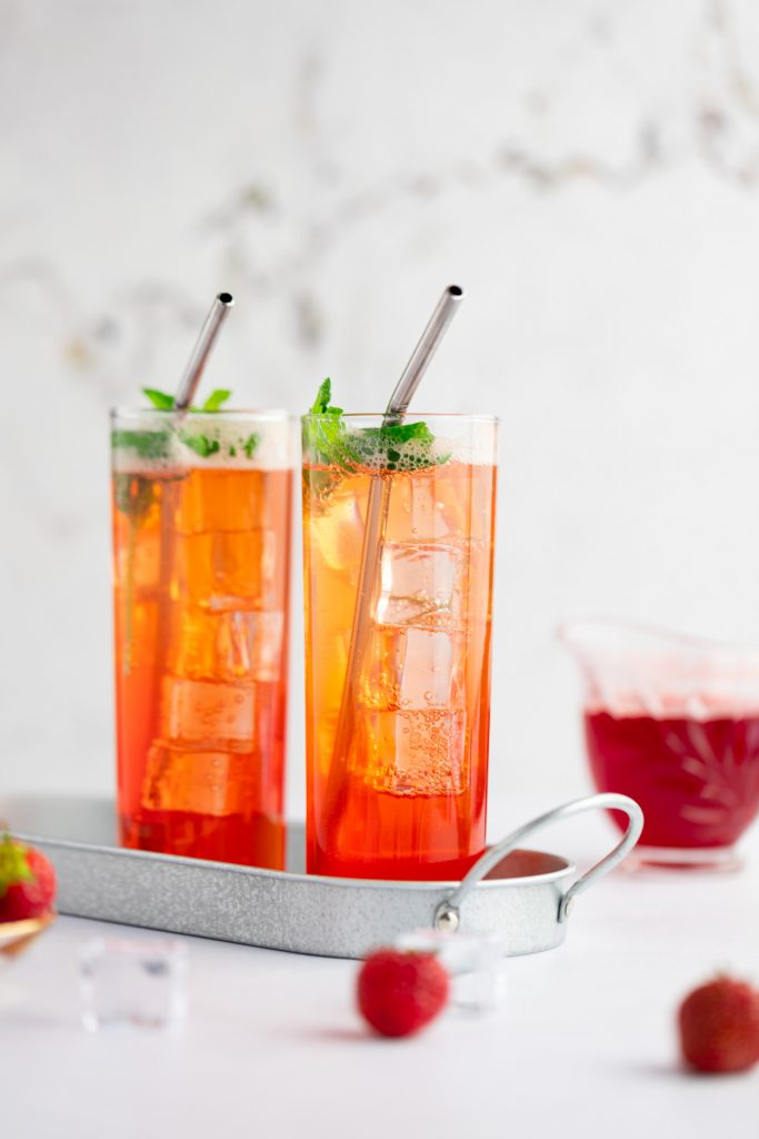 Two strawberry mojito mocktails on a metal tin tray, with strawberry syrup in the background and strawberries in the foreground.