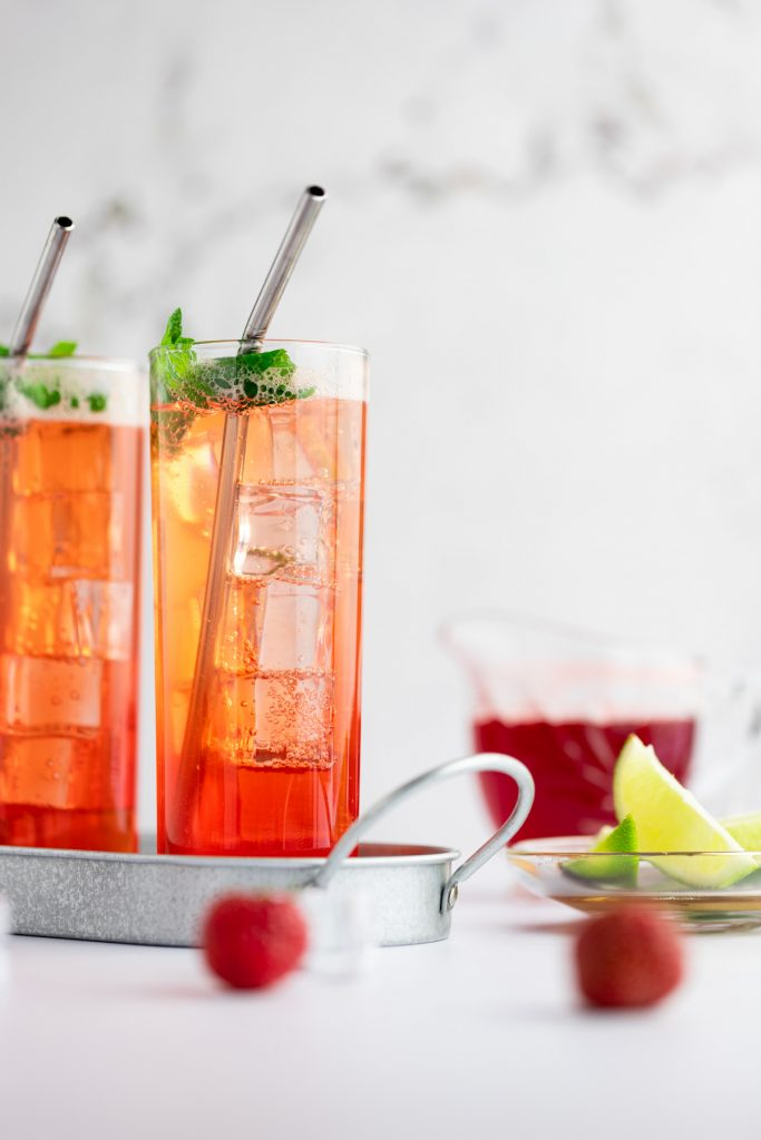 A couple strawberry mocktails on a metal tray next to a dish of lime slices, strawberries and syrup.