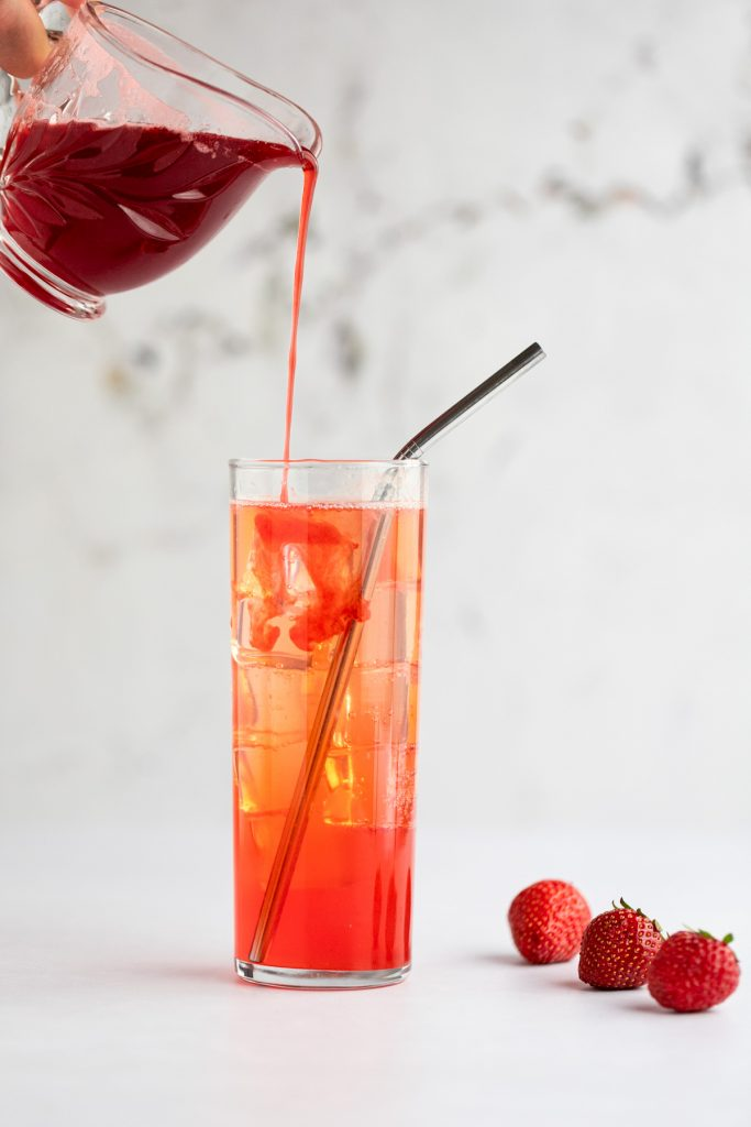 Action shot of a hand holding a glass jar of strawberry syrup and pouring it into a moijto glass filled with ice and a metal straw, next to three fresh strawberries.
