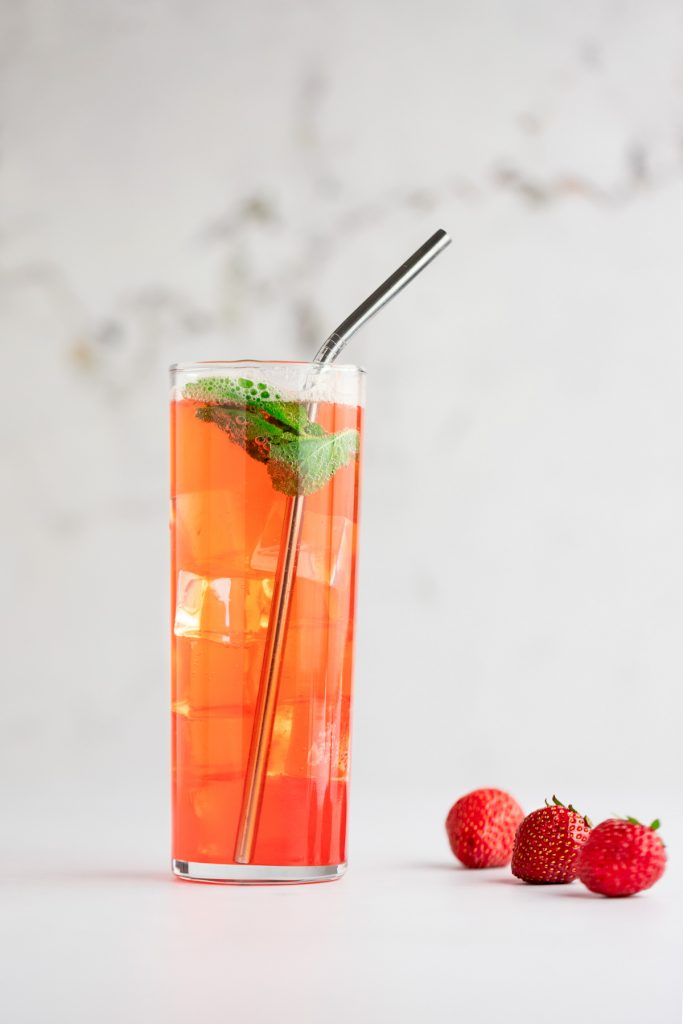A virgin strawberry mojito in a tall mojito glass, with a metal straw, ice and garnished with fresh mint, with three strawberries lying beside the glass.