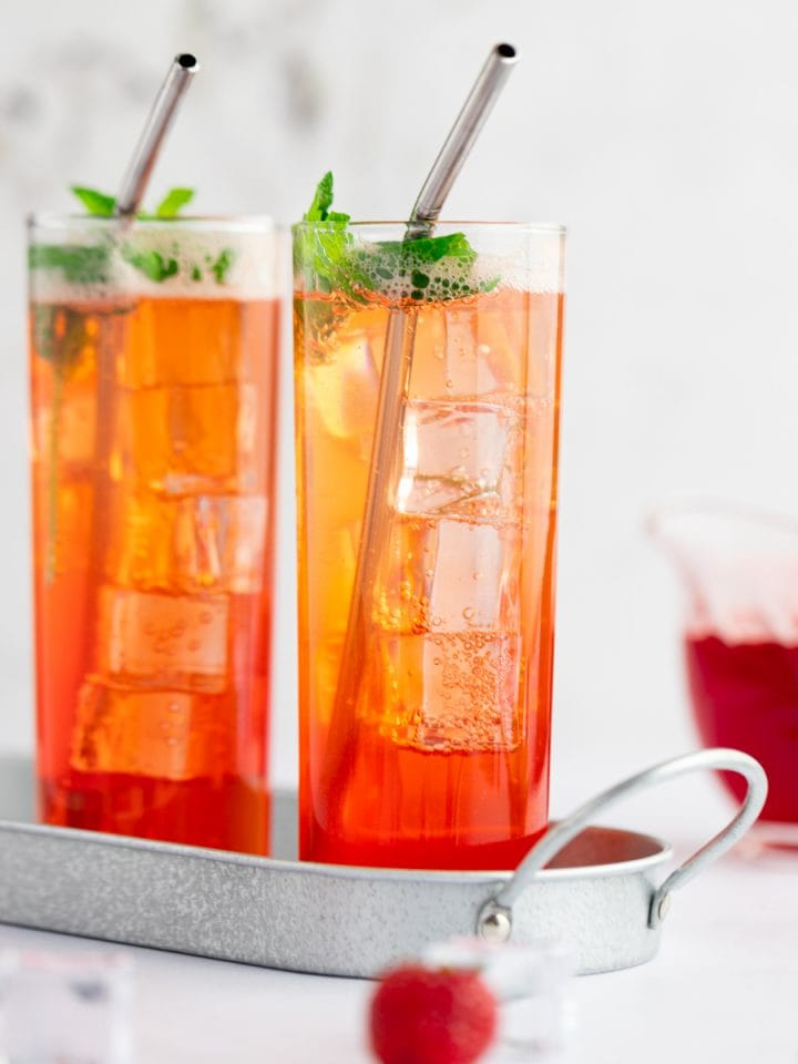 Two virgin strawberry moijito glasses in a tin serving tray, with strawberries scattered beside the mocktails.