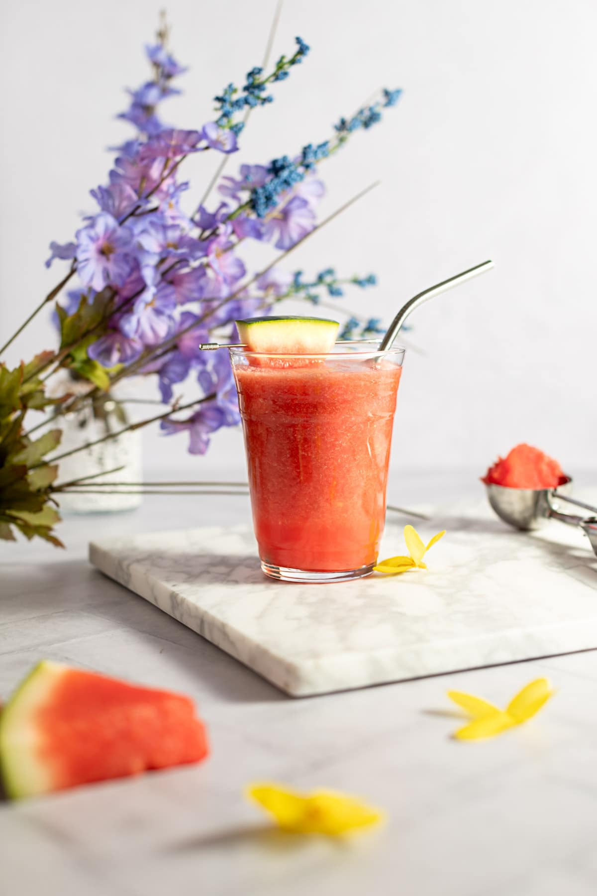 A watermelon pineapple smoothie, garnished with a slice of watermelon, on a grey marble board, with purple flowers in the background.