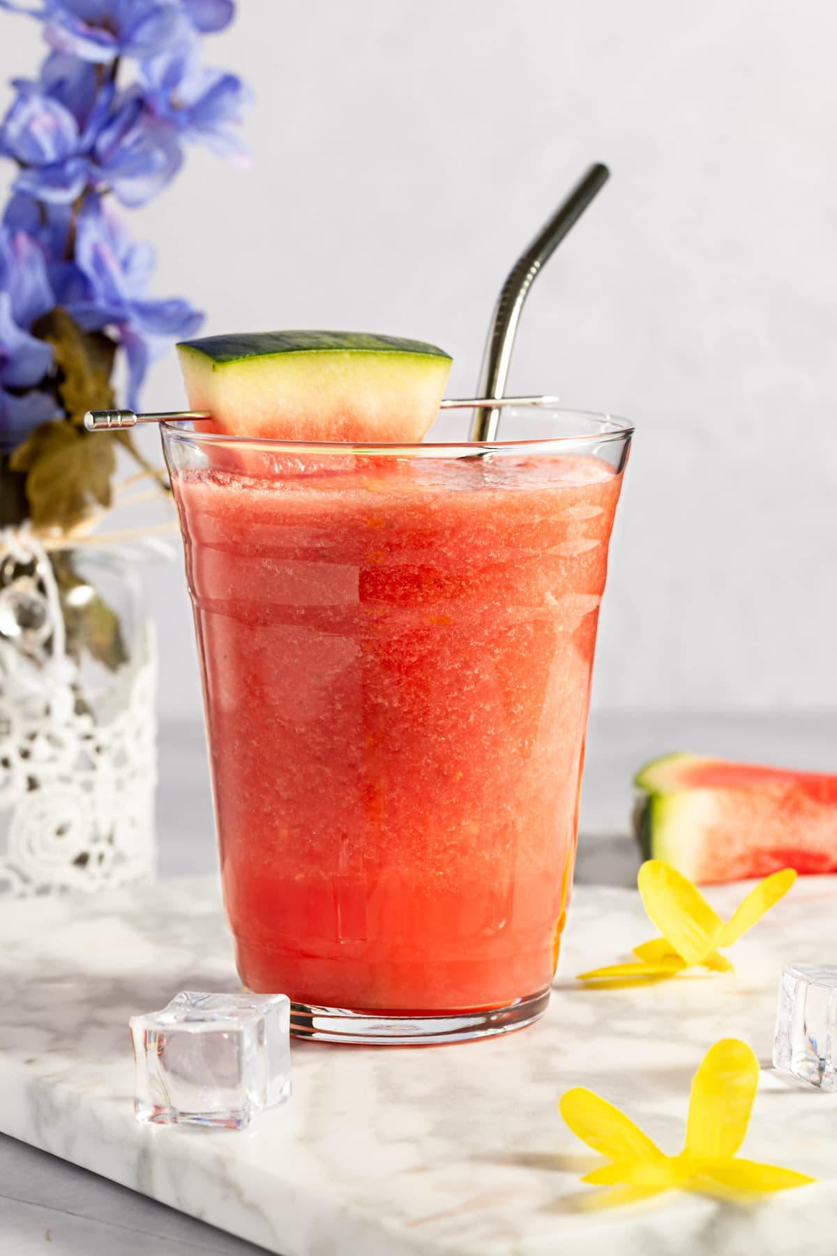Up close photo of a watermelon and pineapple smoothie with ice cubes and yellow flowers scattered around and a vase in the background.